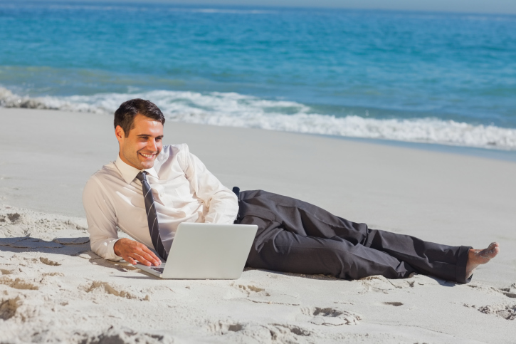 Young businessman lying on the sand using his laptop